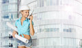 Woman in hard hat holding drawing rolls, talking Royalty Free Stock Photo