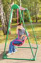 Woman has a rest on a swing in the garden Stock Photos
