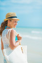 Woman with hat and bag at seaside looking into distance happy young Stock Photos