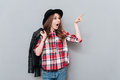 Woman in hat and plaid shirt pointing finger away