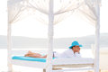Woman in hat relaxing on bed at the sea Stock Images