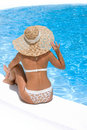 Woman in hat relaxing beside pool