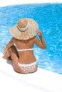 Woman in hat relaxing beside pool