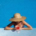 Woman in hat relaxing at the pool with cosmopolitan cocktail Stock Photo