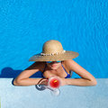 Woman in hat relaxing at the pool with cosmopolitan cocktail Royalty Free Stock Photo