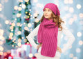 Woman in hat and scarf over christmas tree lights winter holidays people concept young background Royalty Free Stock Photo