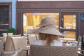 Woman with hat sitting alone on restaurant terrace Royalty Free Stock Photo
