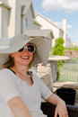 Woman in Hat and Sunglasses Sitting on Patio Royalty Free Stock Photo