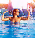 Woman have fun in the pool beautiful having making water splash by hands enjoying hot summer day swimming summertime holiday Royalty Free Stock Photos