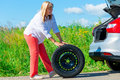 Woman have prepared to replace the spare wheel year old Royalty Free Stock Image