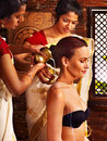 Woman having ayurvedic spa treatment pouring milk Royalty Free Stock Images