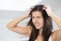 Woman having a bad hair day grimacing in disgust as she looks in the mirror and runs her hands through her Stock Image