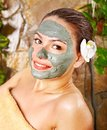 Woman having clay facial mask apply by beautician. Royalty Free Stock Image