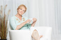 Woman having coffee while relaxing at home happy middle aged on the couch enjoying a cup of Stock Image