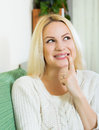 Woman having cunning look indoors smiling young on couch Royalty Free Stock Photos