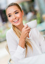 Woman having a cup of coffee happy at restaurant Stock Image
