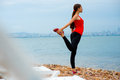 Woman having exercise on the beach young sea and city background in cloudy weather Stock Photos