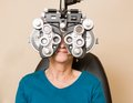 Woman having an eye exam senior looking through phoropter during Royalty Free Stock Photo