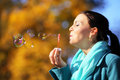 Woman having fun blowing bubbles in autumnal park happiness carefree and autumn young soap on a bright yellow leaves background Royalty Free Stock Photo