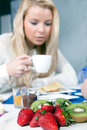 Woman having a healthy fruity breakfast with serving of fresh ripe red whole strawberries and sliced kiwifruit on plate in the Royalty Free Stock Photos