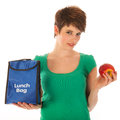 Woman having lunch with fruit bag is eating an apple Royalty Free Stock Images