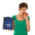 Woman having lunch with fruit bag is eating an apple Stock Image