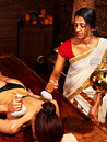 Woman having massage with pouch of rice ayurveda Royalty Free Stock Photography