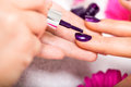 Woman having a nail manicure in a beauty salon with closeup view of beautician applying rich purple varnish with an Royalty Free Stock Image