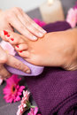 Woman having a pedicure treatment at a spa or beauty salon with the pedicurist massaging the soles of her feet with pumice stone Royalty Free Stock Photo