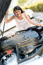 Woman having problems with her car and looking under the hood Stock Photography