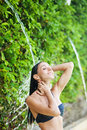 Woman having shower under tropical waterfall bali Stock Photography