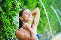 Woman having shower under tropical waterfall Royalty Free Stock Photo