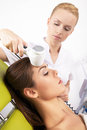 Woman having a stimulating facial treatment from a therapist portrait of attractive beautiful young adult brunette women on the Stock Images