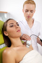 Woman having a stimulating facial treatment from a therapist portrait of attractive beautiful young adult brunette women on the Stock Photo