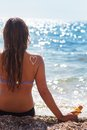 Woman having sun bathes with sunscreen spf filtred closeup picture of tan lotion on back over blue sea background Stock Photo