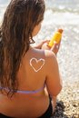 Woman having sun bathes with sunscreen spf filtred pretty is sitting on the sea coast lotion on her back Royalty Free Stock Photo