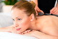 Woman having wellness spa hot stone massage in beauty looking relaxed Stock Image