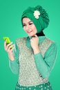 Woman with head scarf holding mobile phone Royalty Free Stock Photo