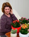 Woman with a headache near the pot plants Royalty Free Stock Photo