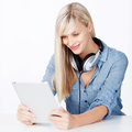Woman with headphone and tablet smiling holding an over white background Stock Photo