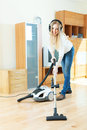 Woman in headphones cleaning with vacuum cleaner blonde on parquet floor Stock Photography