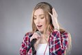 Woman with headphones and microphone singing isolated on gray Royalty Free Stock Image