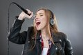 Woman with headphones and microphone singing isolated on gray Royalty Free Stock Photography