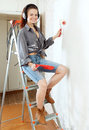 Woman in headphones with roller on stepladder portrait of young the interior Royalty Free Stock Images