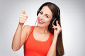 Woman with headphones showing thumbs up casual young over grey background Royalty Free Stock Image