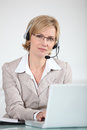 Woman with headset on laptop Royalty Free Stock Images