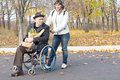 Woman helping a disabled pensioner in a wheelchair pushing him along the street his as he clutches paper bag Royalty Free Stock Photography