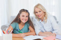 Woman helping her daughter doing her homework in living room Stock Photography