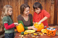 Woman helping kids to carve jack-o-lanterns Royalty Free Stock Photo