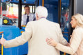 Woman helping senior man to board bus whilst holding his arm smiling Stock Image